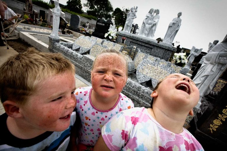 """Siblings in front of their grandfather's grave in Ballymote, Co. Sligo. Charlie Joseph Ward, """"better known as the Scrapper Ward"""", is carved on the grave, was one of the best fighters of the County. Many people contributed with money to build a marble and granite grave. Some Travellers' grave, bigger than this one, cost more than £ 40.000."""