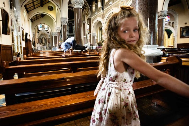 Despite the silence and holiness of the church, children play jumping on the benches. Even during the church service parents struggle to repress their exuberance.
