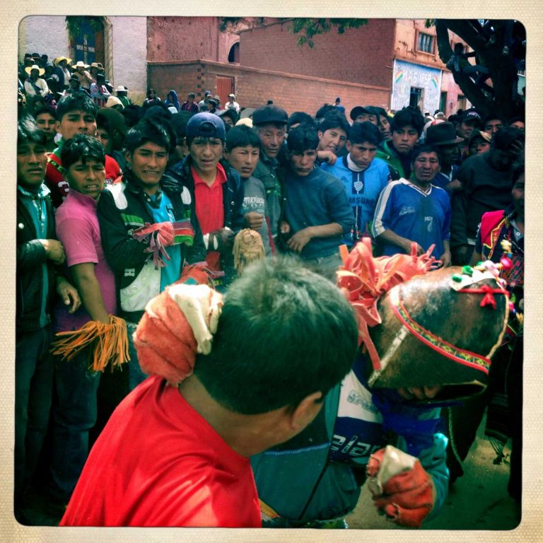 Pocoata, Potosì department, Bolivia. May 2014. A fight is going on while a group of men watches. On the stairs of the church in the background, women have gathered to watch the fighting. Farmers from surrounding villages gather in Pocoata to celebrate Tinku, the traditional festival of Pachamama (Mother Earth). According to the people of the Andes, Mother Earth demands human blood to be fertilized.