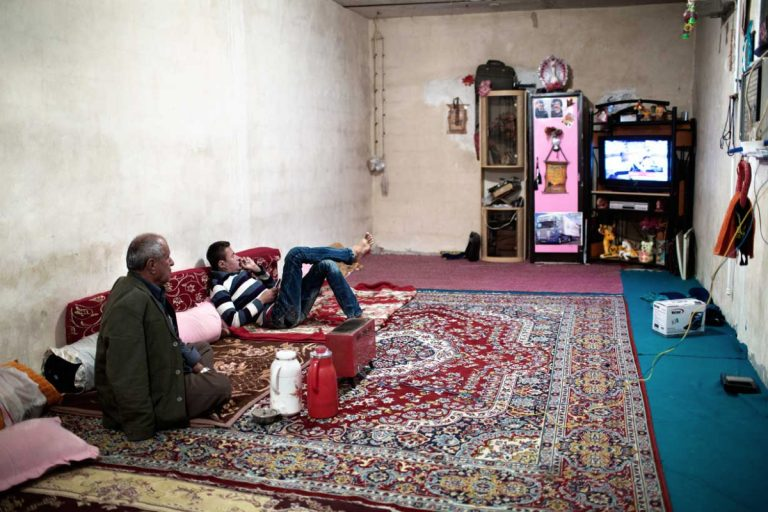 Ghaffar and his father watching TV at home. Iran, November 2014.