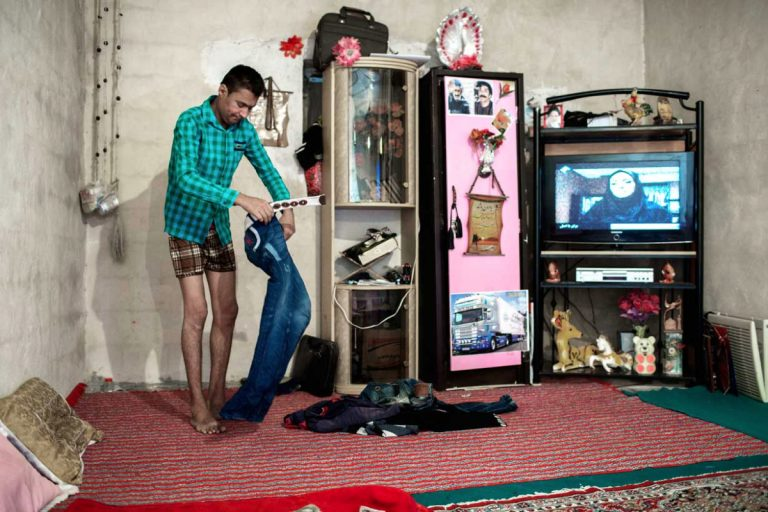 Ghaffar getting dressed in his home. Iran, November 2014.