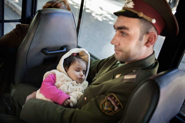 Stepanakert. A civil policeman on the bus with his daughter. Nagorno-Karabakh's Police has two branches: the civil one, wearing green and grey uniforms, and the military one, wearing dark uniforms.