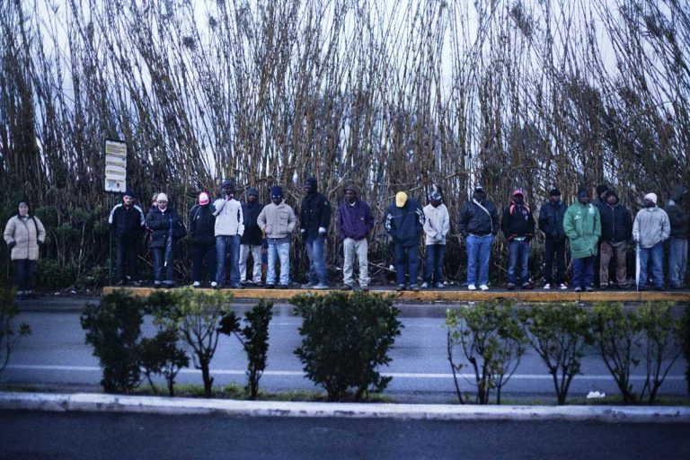 Licola, sunrise. People waiting at a bus stop.