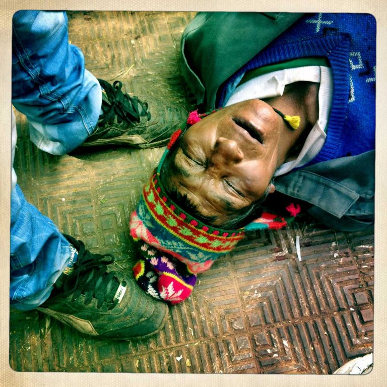 Pocoata, Potosì department, Bolivia. May 2014. Probably too drunk to fight, this man lies passed out on the ground in Pocoata. Farmers from surrounding villages gather in Pocoata to celebrate Tinku, the traditional festival of Pachamama (Mother Earth). According to the people of the Andes, Mother Earth demands human blood to be fertilized.
