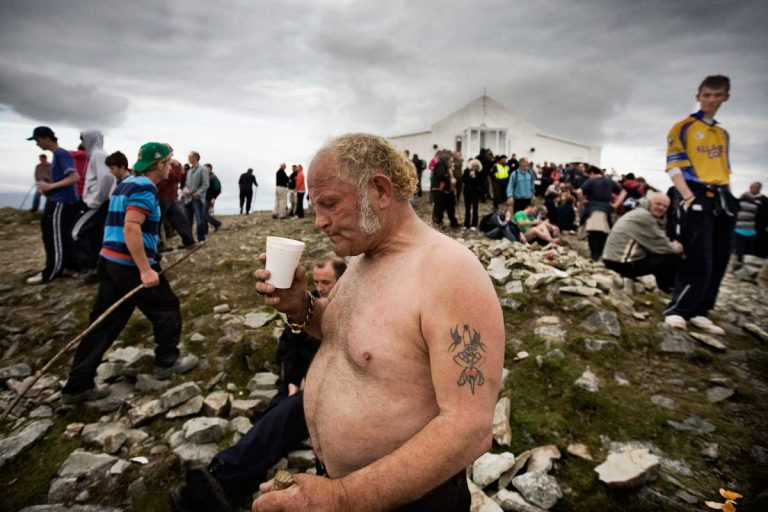 Man drinking after reaching the summit of Croagh Patrick. On 'Reek Sunday', the last Sunday in July, over 25,000 pilgrims visit the Reek. Many Travellers arrive on Saturday in order to spend time with relatives or friends living far away and that can be met primarily during religious events.