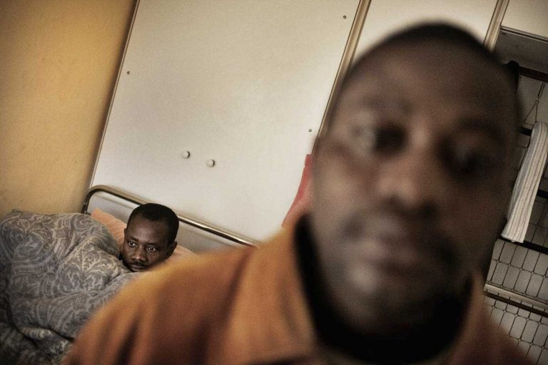 Caritas Centre in Castel Volturno. Ghanian affected by polio in bed. In the foreground, Maxwell Amponsah. He lives in the medical ward recovering from a beating he suffered in Rosarno where he was assaulted by three Italians.