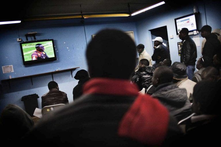 People watching the African Football Cup in a betting centre. Half of the foreigners living in Castel Volturno are from Ghana.