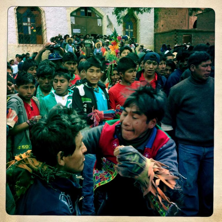 Pocoata, Potosì department, Bolivia. May 2014. The fighting is going on while a group of men watching in the background. At the church stairs a bit more far behind, women have gathered to watch the fighting. Farmers from surrounding villages gather in Pocoata to celebrate Tinku, the traditional festival of Pachamama (Mother Earth). According to the people of the Andes, once a year Mother Earth demands human blood to be fertilized.