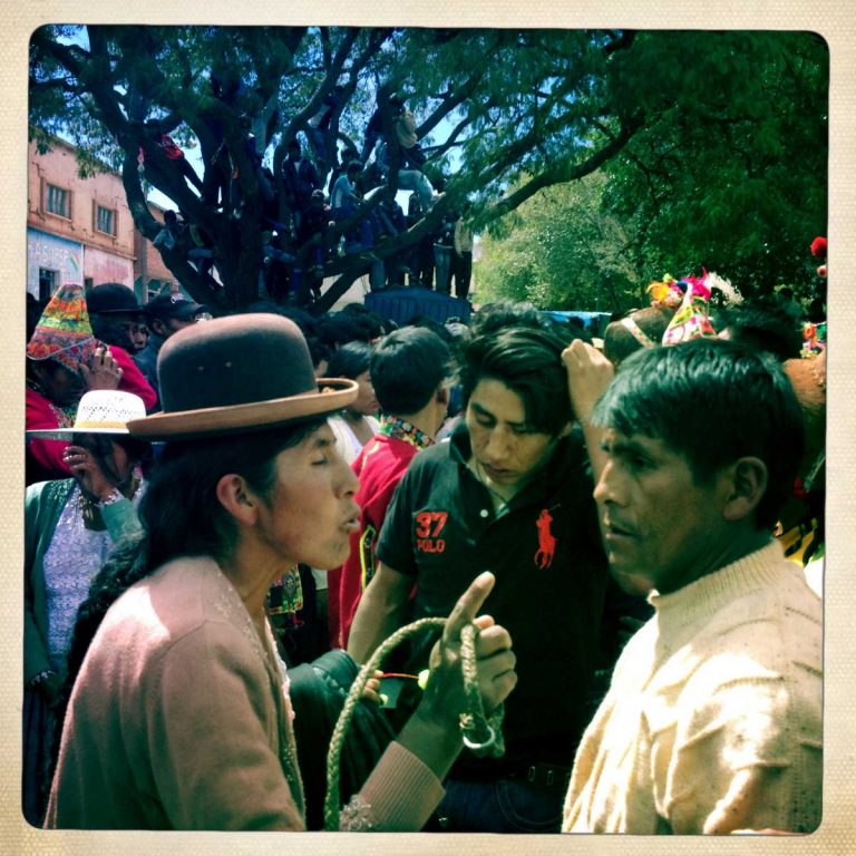 Pocoata, Potosì department, Bolivia. May 2014. A woman tries to keep the order while arguing with an aspiring fighter. She has a traditional whip in her hand, showing that she means what she is saying. Farmers from surrounding villages gather in Pocoata to celebrate Tinku, the traditional festival of Pachamama (Mother Earth). According to the people of the Andes, once a year Mother Earth demands human blood to be fertilized.